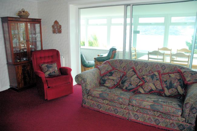 Strathardle, Lochcarron, has a comfortable and homely living room with a large conservatory immediately adjacent.