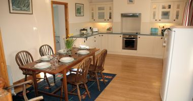 Gardener's Cottage, Lochcarron, has a spacious and well equipped kitchen/dining room with the entrance conservatory immediately adjacent.